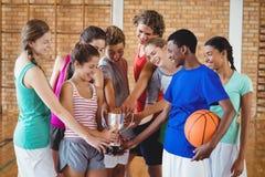 Den upphetsade högstadiet lurar den hållande trofén i basketdomstol arkivbild