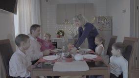 Den upphetsade lyckliga familjen av sex tycker om den festliga julmatställen i älskvärd hemtrevlig kökberömarmosphere i jultomten stock video
