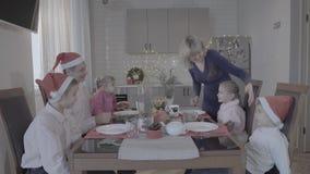 Den upphetsade lyckliga familjen av sex tycker om den festliga julmatställen i fantastisk hemtrevlig kökberömarmosphere i jultomt lager videofilmer
