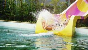 Den upphetsade mannen i solglasögon som ner glider den snabba vattenglidbanan i rolig aqua, parkerar att skrika på en varm sommar lager videofilmer