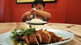 Den upphetsade pojken att äta ris med grillad höna arkivfoton