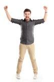 Den upphetsade stiliga mannen med armar lyftte i framgång Royaltyfri Foto