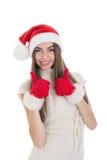 Den upphetsade tonårs- flickan med jultomtenhattvisning tummar upp Royaltyfria Foton