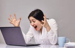 Den upphetsade unga härliga kvinnan är chockad vid vad hon såg på hennes skärm Arkivfoto