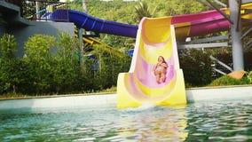 Den upphetsade unga kvinnan som ner glider den snabba vattenglidbanan i rolig aqua, parkerar att skrika på en varm sommardag lång lager videofilmer