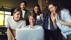 Den upphetsade unga mannen ser bärbar datorskärmen, fröjd, och uttrycka lycka, gratulerar hans kollegor honom stock video
