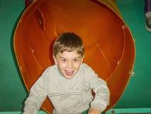 Den upphetsade unga pojken visar hans glädje som kommer ut ur en rörglidbana Arkivfoto