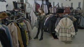 Den upphetsade unga tonåringflickan som gör shopping på hennes fria tid i ett litet, shoppar lagret - stock video