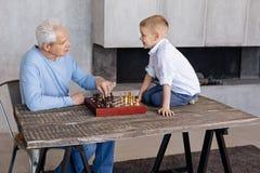 Den upphetsade uppmärksamma pojken som lyssnar till hans morföräldrar, föreläser Arkivfoto