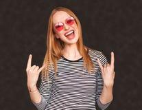 Den upphetsade visningen för ung kvinna vaggar gest royaltyfri foto