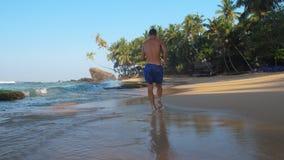 Den upphetsande barfota mannen kör längs kustlinjen under blå himmel arkivfilmer