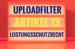 Den upplysta panelen med de tyska orden Uploadfilter Artikel 13 Leistungsschutzrecht i engelskt laddar upp extra filterartikel 13 Arkivbild