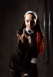 Den uppnosiga härliga sexiga katolska nunnan visar långfingret Religiöst begrepp Arkivfoton