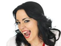 Den uppnosiga härliga unga latinamerikanska kvinnan som drar dumbom, vänder mot och ut klibbar tungan Arkivbild