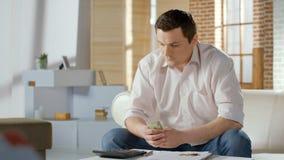 Den upprivna affärsmannen i problem som räknar pengar, skuld intecknar på, lånet, konkurs Arkivfoton