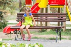 Den upprivna flickan bet hennes kant, medan sitta på bänk på bakgrunden av lekplatsen Arkivfoton