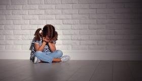 Den upprivna ledsna ledsna barnflickan i spänning gråter på en tom mörk vägg royaltyfria bilder