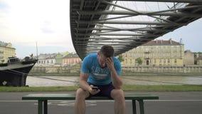 Den upprivna mannen mottar meddelandet som sitter en bänken mot floden lager videofilmer