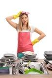 Den upprivna unga kvinnan bak en vask fyllde med smutsiga plattor arkivbild