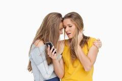 Den upprivna unga kvinnan som ser hennes mobiltelefon, consolded vid hennes vän royaltyfria bilder