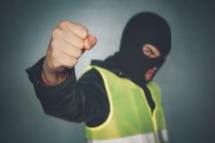 Den upproriska personen som protesterar i en maskering visar hans näve gula tumulter för västprotestgata fransk rotation Ilsket h arkivfoto