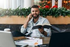 Den uppsökte gladlynta hipstermannen sitter på tabellen framme av bärbara datorer och att tala på mobiltelefonen, medan rymma den arkivbild