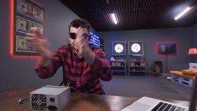 Den uppsökte grabben applåderar till kameran som har asken av strömförsörjning med det pålagda skrivbordet för kylare lager videofilmer
