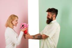 Den uppsökte hipsteren ger bukettblommor till flickvännen Mannen med skägget gratulerar ferie för kvinnafödelsedagårsdag Arkivfoton