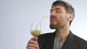 Den uppsökte mannen dricker detoxsmoothien, sunt livsstilbegrepp coctail från grönsaken och frukt långsam rörelse arkivfilmer