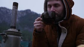Den uppsökte mannen dricker te i turist- läger i bergdalen Lopp i den kalla säsongen som en livsstil långsamt stock video