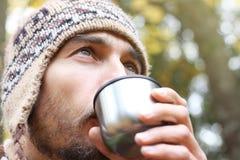 Den uppsökte mannen i ull stucken hatt dricker fast beslutsamt varmt te, eller kaffe från rånar, sid sikten på framsidan, bakgrun arkivfoto