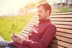 Den uppsökte mannen som sitter på bänk parkerar in, med telefonen i händer arkivfoton