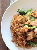 Den uppståndelse stekte plana risnudeln med soya och griskött i den vita maträtten på den färgglade trätabellen i thai kallat `-b royaltyfria foton