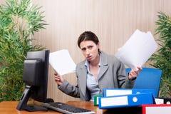 Den upptagna affärskvinnan i kontoret under spänning arkivbild