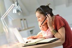 Den upptagna affärskvinnan med behandla som ett barn arbete på bärbara datorn Royaltyfri Foto