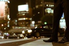 Den upptagna affärsmannen lägger benen på ryggen att vänta som korsar den berömda Shibuya korsningen, Tokyo, Japan arkivbilder