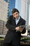 Den upptagna affärsmannen som rymmer den digitala minnestavlan och mobiltelefonen, överansträngde utomhus Royaltyfri Fotografi