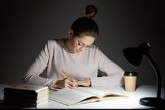 Den upptagna freelanceren skrivar om infrormation in i notepaden, förbereder artikeln för publikation, läser böcker, skriver någr royaltyfri foto