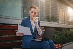 Den upptagna kvinnan är bråttom, henne har inte tid, henne ska äta mellanmålet utomhus Arbetare som äter och arbetar med Royaltyfria Bilder