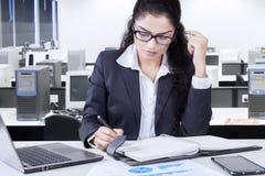 Den upptagna kvinnliga entreprenören skriver en anmärkning arkivbild