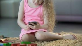 Den upptagna lilla flickan som använder den mobila grejen som spelar spelar på smartphonen, teknologi lager videofilmer