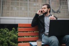 Den upptagna mannen är bråttom, honom har inte tid, honom ska äta mellanmålet utomhus Arbetare som äter och arbetar med Arkivbilder