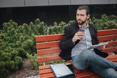Den upptagna mannen är bråttom, honom har inte tid, honom ska äta mellanmålet utomhus Arbetare som äter och arbetar med Arkivfoto