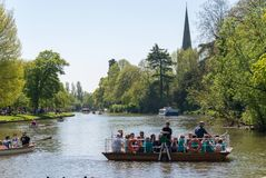 Den upptagna manuella färjan korsar den upptagna floden med träd och kyrkan i bakgrund royaltyfri foto