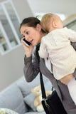 Den upptagna modern som rymmer henne, behandla som ett barn och talar på telefonen Royaltyfri Foto