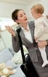 Den upptagna modern som talar till henne, behandla som ett barn och på telefonen Arkivbild