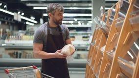 Den upptagna representanten sätter bröd på hyllor i bageriavdelning i matlager, den skäggiga grabben bär förklädet sälja stock video