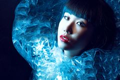 Den ursnygga asiatiska modellen med härligt smink och moderiktig frisyr med frans som bär den utsmyckade glänsande iskalla ställn royaltyfri foto