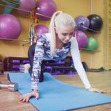 Den ursnygga blondinen som värmer upp och gör som är någon, skjuter ups idrottshallen Arkivfoto