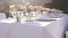 Den ursnygga brölloptabellinställningen för boten som utomhus äter middag, dekorerade med blommor arkivfilmer